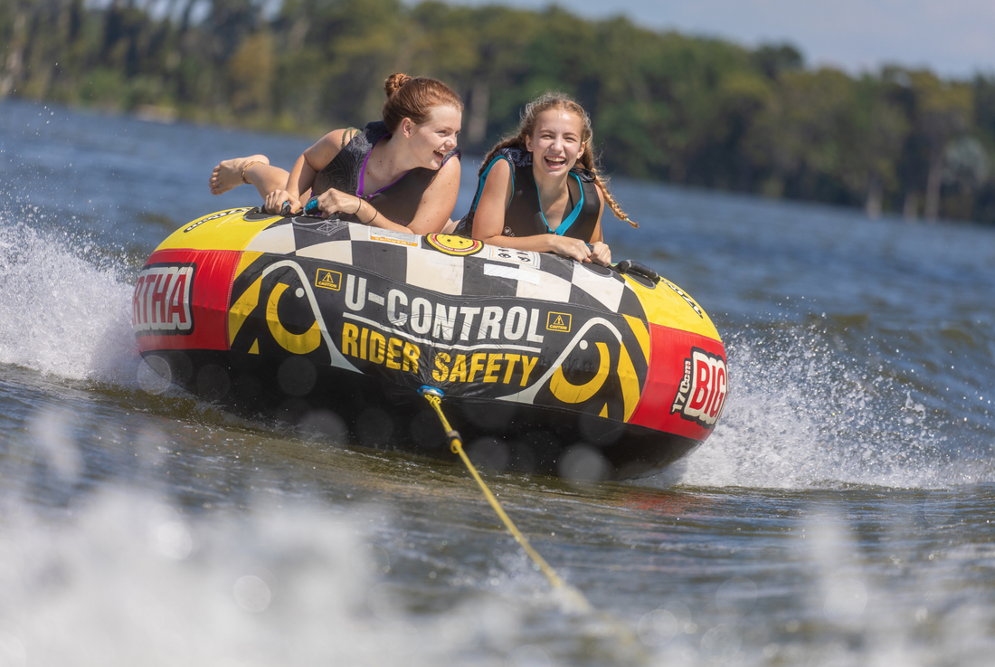 Picture of two girls tubing on the lake